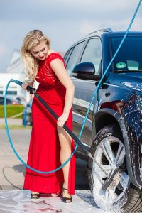woman cleaning car with pressure washer
